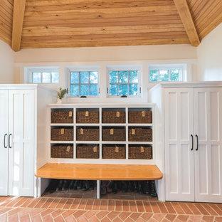 Foto på ett stort vintage kapprum, med vita väggar, tegelgolv, en enkeldörr, en lila dörr och rött golv