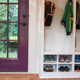 На фото: тамбур в классическом стиле с белыми стенами, кирпичным полом, одностворчатой входной дверью, фиолетовой входной дверью и красным полом с