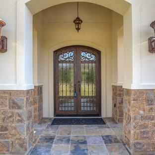 Diseño de puerta principal mediterránea, grande, con puerta doble, puerta metalizada, paredes beige, suelo de pizarra y suelo negro