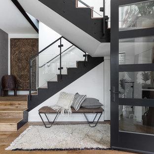 Réalisation d'un hall d'entrée chalet avec un mur blanc, un sol en bois clair et une porte en verre.