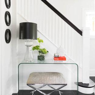 Idee per un ingresso tradizionale di medie dimensioni con pareti bianche, pavimento in gres porcellanato e pavimento nero