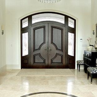 トロントの巨大な両開きドアトランジショナルスタイルのおしゃれな玄関ロビー (白い壁、ライムストーンの床、濃色木目調のドア) の写真