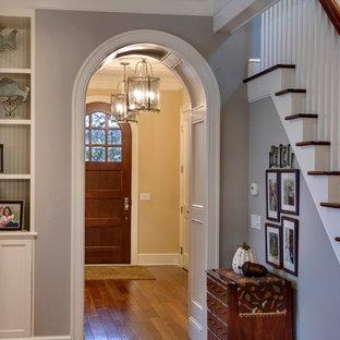 Entryway - beach style medium tone wood floor entryway idea in Grand Rapids with yellow walls and a dark wood front door