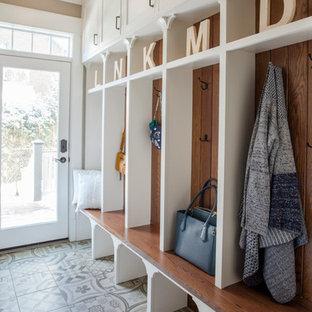 Foto på ett mellanstort vintage kapprum, med beige väggar, en enkeldörr, glasdörr, flerfärgat golv och klinkergolv i porslin