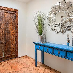 Стильный дизайн: прихожая в стиле фьюжн с двустворчатой входной дверью, входной дверью из дерева среднего тона и оранжевым полом - последний тренд