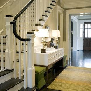 Diseño de entrada clásica con paredes beige, suelo de madera oscura y suelo negro