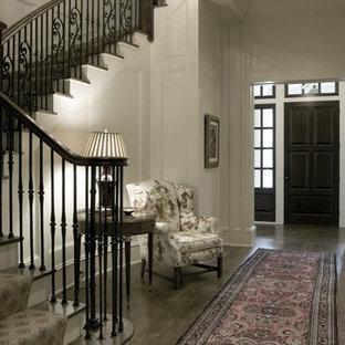 На фото: фойе среднего размера в классическом стиле с белыми стенами, темным паркетным полом, одностворчатой входной дверью, входной дверью из темного дерева и коричневым полом