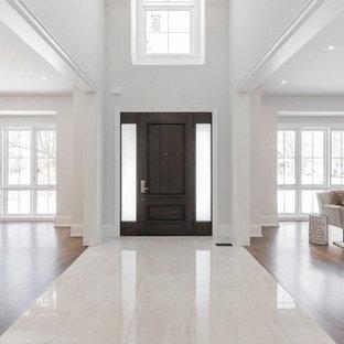 Inspiration för stora klassiska ingångspartier, med vita väggar, marmorgolv, en enkeldörr, en brun dörr och gult golv