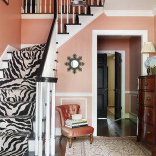 Aménagement d'un hall d'entrée classique avec un mur rose, un sol en bois foncé et une porte simple.