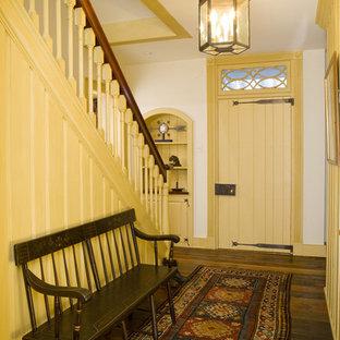 Réalisation d'une entrée champêtre de taille moyenne avec un couloir, un mur blanc, une porte simple, une porte jaune et un sol en bois brun.