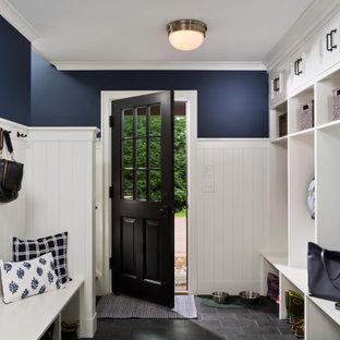 ボストンの広い片開きドアトラディショナルスタイルのおしゃれなマッドルーム (青い壁、スレートの床、黒いドア、黒い床、塗装板張りの壁) の写真