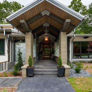 Ispirazione per una porta d'ingresso stile marino di medie dimensioni con pareti con effetto metallico, pavimento in cemento, una porta singola e una porta in legno bruno