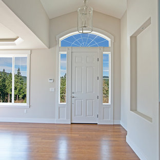 Inspiration for a large craftsman bamboo floor entryway remodel in Seattle with a white front door and white walls