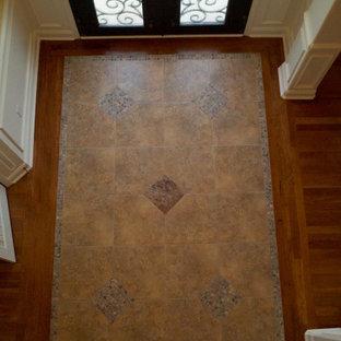 Inspiration för mellanstora klassiska foajéer, med gula väggar, klinkergolv i porslin, en dubbeldörr och en svart dörr