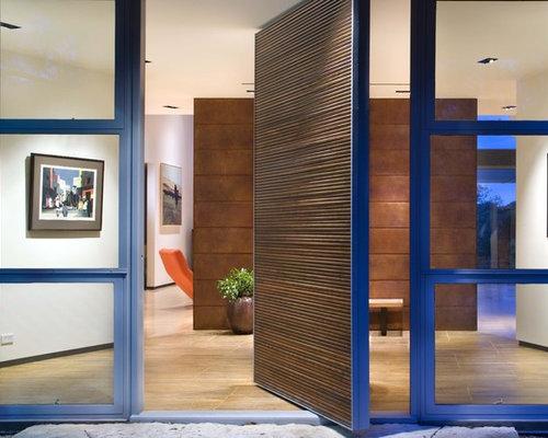 Minimalist Pivot Front Door Photo In Austin With A Medium Wood Front Door