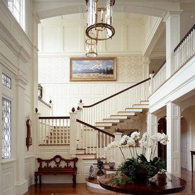Example of a classic dark wood floor foyer design in Boston with white walls