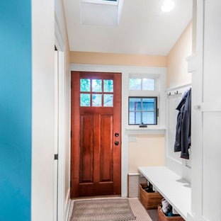 Small arts and crafts ceramic tile entryway photo in Omaha with yellow walls and a dark wood front door