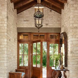 Inspiration for a mediterranean medium tone wood floor single front door remodel in Austin with a medium wood front door