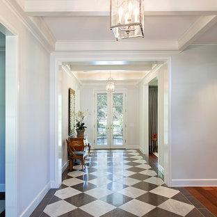 オースティンの広いトラディショナルスタイルのおしゃれな玄関ホール (白い壁、マルチカラーの床、クッションフロア) の写真