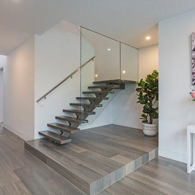 Entryway - contemporary brown floor entryway idea in Melbourne with white walls and a dark wood front door