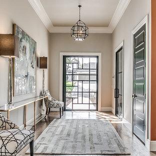Inspiration pour un hall d'entrée traditionnel avec un mur gris, un sol en bois brun, une porte pivot, une porte en verre et un sol marron.
