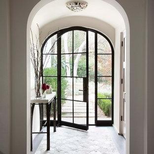Cette photo montre un vestibule méditerranéen avec un mur blanc, un sol en bois foncé, une porte simple et une porte en verre.