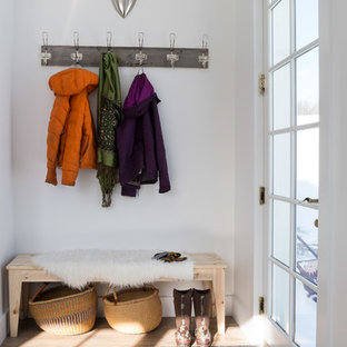 Aménagement d'un hall d'entrée montagne avec un mur blanc, un sol en bois clair, une porte simple, une porte en verre et un sol beige.
