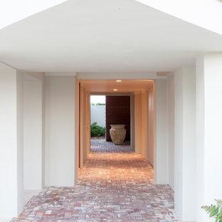 Diseño de entrada marinera con paredes blancas y suelo de ladrillo