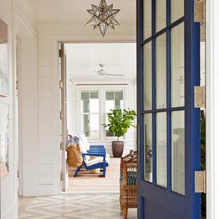 Diseño de puerta principal marinera con paredes blancas, suelo de madera pintada, puerta simple y puerta azul