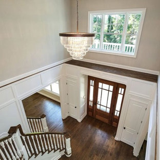 Entryway - large traditional dark wood floor entryway idea in New York with a medium wood front door and white walls