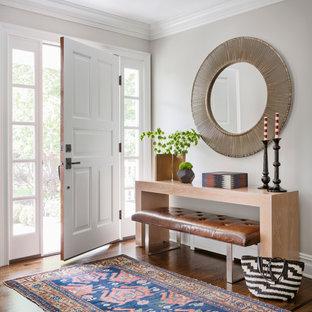 Exemple d'un hall d'entrée chic avec un mur gris, un sol en bois brun, une porte simple et une porte blanche.