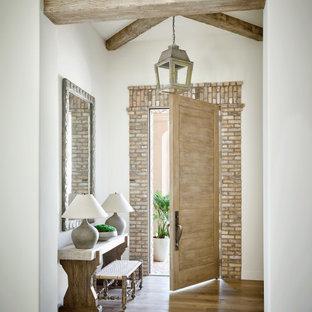 Foto di un ingresso o corridoio con pareti beige, pavimento in legno massello medio, una porta singola, una porta in legno chiaro, pavimento marrone e travi a vista