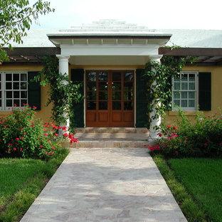 Geräumige Kolonialstil Haustür mit gelber Wandfarbe, Kalkstein, Doppeltür und hellbrauner Holztür in Miami