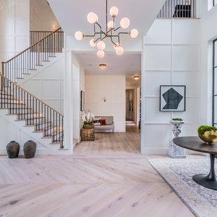 Cette photo montre un très grand hall d'entrée tendance avec un mur blanc, un sol en bois clair, une porte métallisée et une porte double.