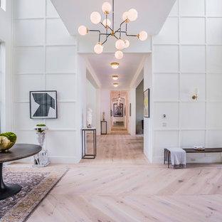 Réalisation d'un très grand hall d'entrée design avec un mur blanc, un sol en bois clair, une porte métallisée et une porte double.