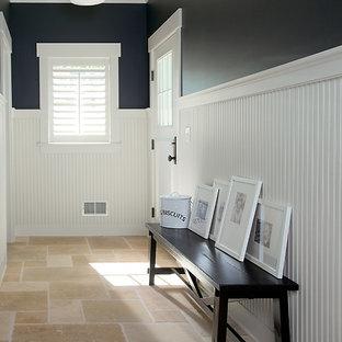グランドラピッズの中くらいの片開きドアビーチスタイルのおしゃれな玄関ホール (白いドア、マルチカラーの壁、トラバーチンの床、茶色い床) の写真