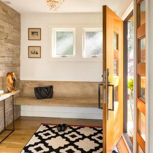Foto de distribuidor actual con paredes blancas, suelo de madera clara, puerta simple y puerta de madera clara