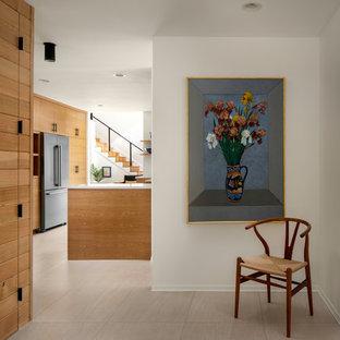 ポートランドの片開きドアミッドセンチュリースタイルのおしゃれな玄関ロビー (白い壁、トラバーチンの床、白い床) の写真
