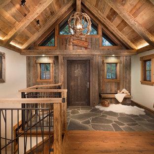 サクラメントの中くらいの片開きドアラスティックスタイルのおしゃれな玄関ロビー (ベージュの壁、濃色木目調のドア、無垢フローリング) の写真