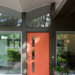 This is an example of a medium sized midcentury front door in Austin with a single front door and a red front door.