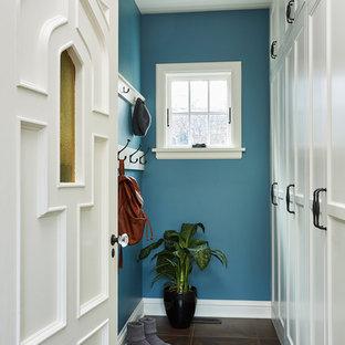 Inspiration för klassiska kapprum, med blå väggar, en enkeldörr, en vit dörr, brunt golv och klinkergolv i porslin