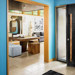 Inredning av en asiatisk entré, med blå väggar, en svart dörr och beiget golv