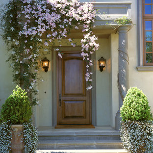 Example of a tuscan entryway design in San Francisco with a medium wood front door