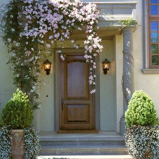 Cette image montre une porte d'entrée méditerranéenne avec une porte simple et une porte en bois brun.