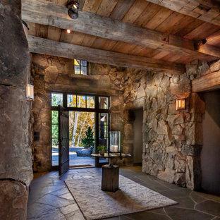На фото: большое фойе в стиле рустика с одностворчатой входной дверью, входной дверью из темного дерева, серым полом и полом из сланца