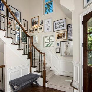 На фото: фойе в стиле современная классика с белыми стенами, темным паркетным полом, одностворчатой входной дверью, входной дверью из темного дерева, коричневым полом и панелями на стенах с