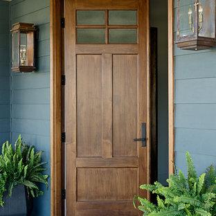 Imagen de puerta principal tradicional, de tamaño medio, con puerta de madera en tonos medios, paredes azules y puerta doble