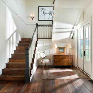 Foto på en lantlig foajé, med vita väggar, mörkt trägolv, en dubbeldörr och en vit dörr