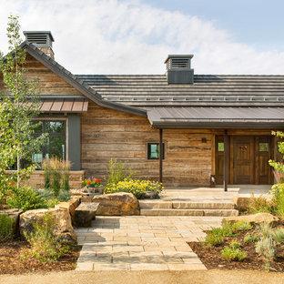 Ispirazione per una porta d'ingresso stile rurale con pareti marroni, una porta singola, una porta in legno bruno e pavimento beige