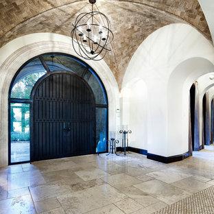 Ejemplo de entrada mediterránea con puerta de madera oscura